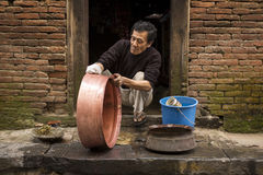 KATHMANDU - NOVEMBER 30: Unkown man cleaning pot in street of Ka Stock Image