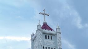 Katholiek kruis bovenop toren katholieke kathedraal Godsdienstige dwarstoren Katholieke Kerk op bewolkte hemel als achtergrond stock videobeelden