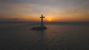Katholiek kruis in het overzees bij zonsondergang stock footage