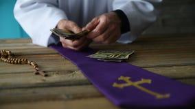 Katholiek priester tellend geld stock videobeelden