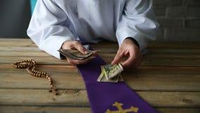 Katholiek priester tellend geld stock footage