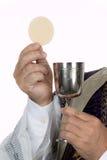 Katholieke priester met miskelk en gastheer bij Heilige Communie stock afbeelding