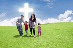 Katholische Familie am Kreuz Stockbild