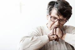 Katholische Großmutter in der Melancholie betend zum Gott mit rotem rosar stockfoto