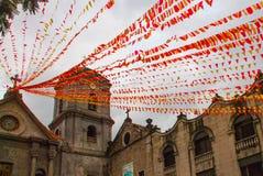 Katholische Kathedrale mit roten Bändern und Flaggen am Abend Manila, Philippinen lizenzfreie stockbilder