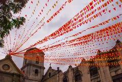 Katholische Kathedrale mit roten Bändern und Flaggen am Abend Manila, Philippinen stockbild