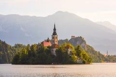 Katholische Kirche in ausgeblutetem See und ausgeblutetes Schloss, Slowenien bei Sonnenaufgang Lizenzfreie Stockbilder