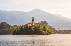 Katholische Kirche in ausgeblutetem See und ausgeblutetes Schloss, Slowenien bei Sunris Lizenzfreie Stockfotos