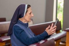Katholische Nonne in einer Kapellenbank und Betrachten einer Tablette, die sie hält lizenzfreie stockfotos