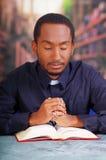 Katholischer Priester, der das traditionelle Hemd des kanzleimäßigen Kragens sitzt mit den gefalteten Händen halten Rosenbeet bei Stockfotografie