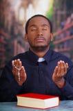 Katholischer Priester, der das traditionelle Hemd des kanzleimäßigen Kragens sitzt mit den gefalteten Händen halten Rosenbeet bei Lizenzfreie Stockfotos
