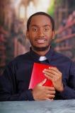 Katholischer Priester, der das traditionelle Hemd des kanzleimäßigen Kragens sitzt und hält die Bibel untersucht Kamera, Religion Stockbilder