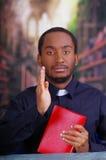 Katholischer Priester, der das traditionelle Hemd des kanzleimäßigen Kragens sitzt und hält die Bibel untersucht Kamera, Religion Lizenzfreie Stockbilder