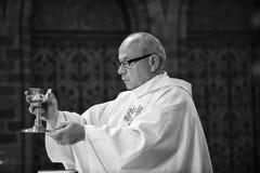 Katholischer Priester mit Messkelchschale lizenzfreies stockbild