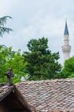 Katholisches hölzernes Kreuz auf das Dach auf Vordergrund und Mustafa Pasha Mosque-Turm auf dem Hintergrund in Skopje, Mazedonien lizenzfreie stockfotografie