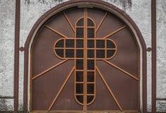 Katholisches oder christliches Kreuz an der Tür einer verlassenen Kirche lizenzfreie stockfotos