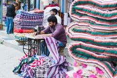 KATMANDU, NEPAL - ABRIL DE 2015: Colchón de costura del hombre Nepali en la calle foto de archivo libre de regalías