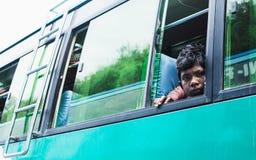 KATMANDU, NEPAL - APRIL 2015: jonge droevige jongen die uit het busvenster kijken stock afbeelding