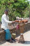 KATMANDU, NEPAL - 18. APRIL 2013: Verkäuferkokosnüsse in traditionellem Lizenzfreie Stockfotografie