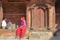 KATMANDU, NEPAL - 14 DE ENERO DE 2015: Un par nepalés que se sienta delante de un templo en Durbar ajusta Foto de archivo