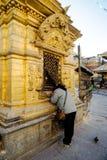 KATMANDU NEPAL - DEC 19, 2010: Kvinna som ber i den Swayambhunath eller apatemplet, Katmandu, Nepal Templet skyddas som Arkivfoto