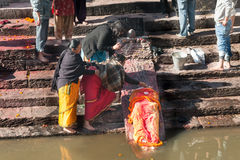 KATMANDU NEPAL - DECEMBER 19, 2012: Lokalt folk för Nepali under kremeringceremonin längs den heliga Bagmati floden i Bhasmeshva Royaltyfri Bild
