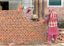 KATMANDU NEPAL - DECEMBER 17, 2012: Murare för arbetare för kvinnor för Nepalikonstruktionsmurare som gör ett murverk med murslev Royaltyfria Bilder