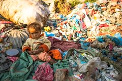 KATMANDU, NEPAL - het Niet geïdentificeerde kind zit terwijl haar ouders aan stortplaats werken Stock Foto