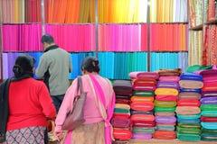 KATMANDU NEPAL - JANUARI 14, 2015: Ett färgrikt tyg shoppar i den gamla staden Arkivfoto