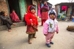 KATMANDU, NEPAL - lokale kinderen dichtbij hun huizen op een slecht gebied van de stad stock foto's