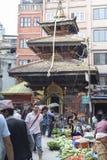 KATMANDU NEPAL - MAJ 15, 2014: Folket shoppar en upptagen gata som framme namnges Ason Tole av Ganesh Shrine, Indra Chowk, Kat Arkivfoto