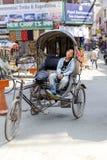KATMANDU NEPAL - MAJ 17, 2014: Trött chaufför för cirkuleringsrickshaw som sover på hans medel på ingången av Thamel område Katma Arkivbild