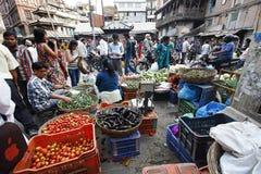 KATMANDU NEPAL-MAY 11, 2014: Lokalt folk som shoppar för livsmedel i den Asan Tol marknaden Royaltyfri Fotografi
