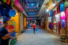 KATMANDU, NEPAL 15 OKTOBER, 2017: Niet geïdentificeerde mensen die in een bezige het winkelen straat met kleurrijke binnen decora Stock Foto's