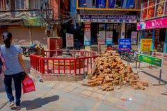 KATMANDU NEPAL OKTOBER 15, 2017: Oidentifierad kvinna gå i de gatorna nästan marknader och en hög av tegelstenar in Royaltyfria Bilder