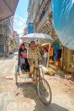 KATMANDU NEPAL OKTOBER 15, 2017: Oidentifierat folk i rickshaw i historisk mitt av staden, i Katmandu, Nepal Royaltyfri Foto