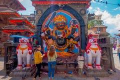 KATMANDU NEPAL OKTOBER 15, 2017: Oidentifierat folk på det fria nästan asfulla skulpturer med en sniden vägg med Arkivbilder