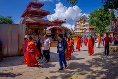 KATMANDU NEPAL OKTOBER 15, 2017: Oidentifierat folk som går i gatorna av staden med några byggnader in Royaltyfria Bilder