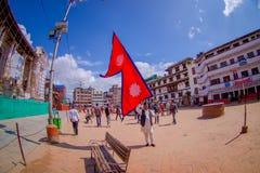 KATMANDU NEPAL OKTOBER 15, 2017: Oidentifierat folk som går i gatorna och en nepalese man som rymmer en flagga i hans Royaltyfri Foto