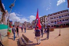 KATMANDU NEPAL OKTOBER 15, 2017: Oidentifierat folk som går i gatorna och en nepalese man som rymmer en flagga i hans Arkivfoto