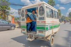 KATMANDU NEPAL OKTOBER 15, 2017: Oidentifierat folk som reser i den tillbaka delen av en rickshaw in i Katmandu, Nepal Arkivbild