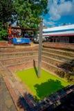 KATMANDU NEPAL OKTOBER 15, 2017: Utomhus- sikt av det konstgjorda dammet med grönt vatten med en sniden pelare i mitt Royaltyfria Bilder