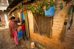 KATMANDU, NEPAL - plaatselijke bevolking dichtbij hun huis op een slecht gebied van de stad royalty-vrije stock afbeelding