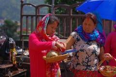 KATMANDU NEPAL - SEPTEMBER 04, 2017: Unidentifed kvinnor som rymmer i deras handkorg med oblations av mat, frukter Fotografering för Bildbyråer