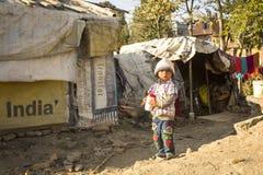 KATMANDU, NEPAL - slecht kind dichtbij hun huizen bij krottenwijken in Tripureshwor-district Royalty-vrije Stock Foto's