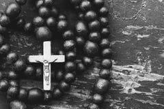 Katolicka różaniec modlitwa z krzyżem na starym czarnym drewnianym tle z przestrzenią dla teksta zdjęcia stock
