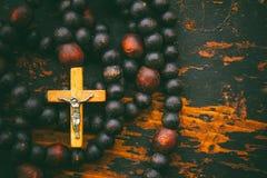 Katolicka różaniec modlitwa z krzyżem na starym czarnym drewnianym tle z przestrzenią dla teksta zdjęcie royalty free