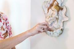 Katolicy zamacza palec w chrzcielnicę zawiera świętą wodę Fotografia Royalty Free