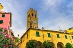 Katolsk kyrka av den San Giovanni Battista chiesaen med klockatornet, färgrika byggnadshus och blommor omkring i den Monterosso v arkivfoton
