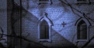 Katolsk kyrka på natten, månskenskuggor royaltyfria foton